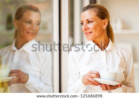 elegant senior businesswoman looking outside of office with coffee - stock photo