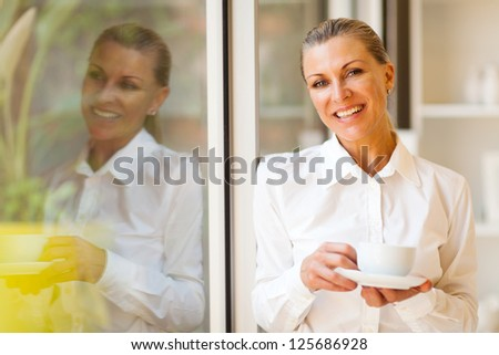 elegant senior businesswoman with coffee in modern office - stock photo