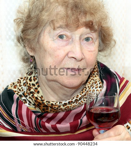 elegant senior lady holding a glass of red wine on a toast - stock photo
