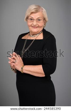 Elegant senior woman. Closeup of beautiful senior woman wearing elegant black dress while standing against grey background - stock photo