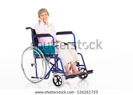 elegant senior woman sitting on wheelchair isolated on white - stock photo