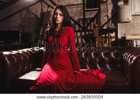 elegant sensual young brunette woman in red dress sitting on leather sofa