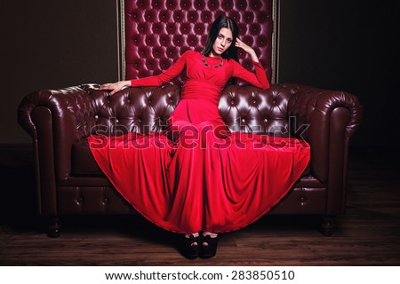 elegant sensual young brunette woman in red dress sitting on leather sofa - stock photo