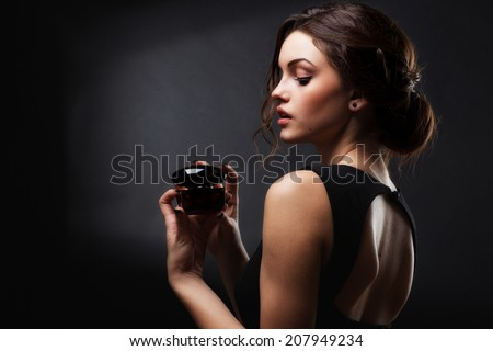 Elegant sensual young woman holding perfume, Beautiful woman face. Perfect makeup. Beauty fashion. Fashion photo - stock photo