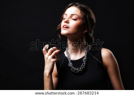 Elegant sensual young woman holding perfume. Fashion photo of young magnificent woman. Girl posing. Studio photo. Perfect Skin. Professional Make-up.Makeup. Fashion Art. Vogue Style.  - stock photo