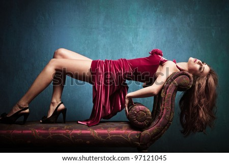 elegant sensual young woman in red dress on recliner indoor shot - stock photo