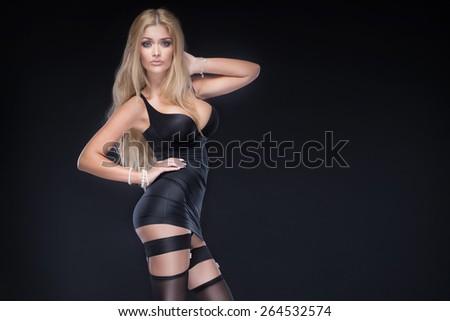 Elegant sexy blonde woman posing in black lingerie. Studio shot. - stock photo