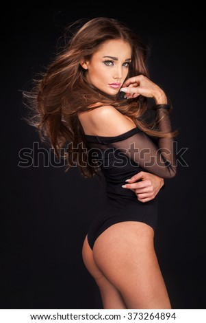 Elegant sexy brunette woman posing in lingerie, looking at camera. Perfect slim body. - stock photo
