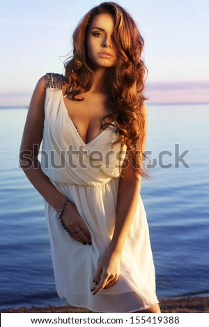 elegant sexy lady. beautiful stunning girl in white dress posing at sea coast against blue sky at sunset                  - stock photo