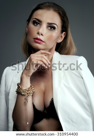 Elegant sexy woman posing in studio, looking at camera. Blonde lady wearing gold jewelry. Beauty portrait. - stock photo