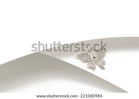 Elegant silver diamante butterfly ornament or brooch with outspread wings displayed on a two-tone silver and white background with copyspace - stock photo