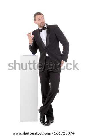 Elegant slender man in a suit and bow tie leaning nonchalantly on a white pedestal with a quizzical charismatic expression