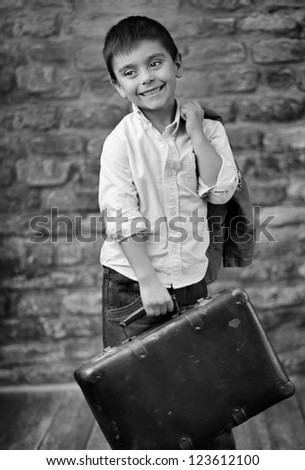 elegant small boy with suitcase - stock photo