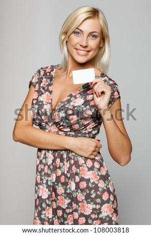 Elegant smiling female showing an empty credit card, over gray background