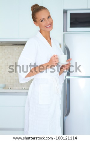 Elegant smiling woman in white robe standing in front of a fridge drinking an early morning cup of coffee