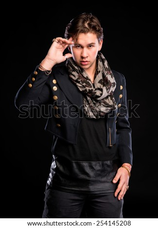 Elegant smiling young handsome man on a dark background - stock photo