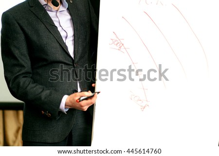 elegant speaker lecturer drawing charts at white board, at meeting, business marketing lecture coaching - stock photo