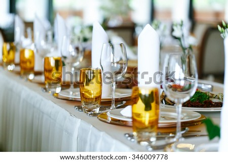 Elegant stylish decorated wedding reception tables with glasses and flowers in vase closeup