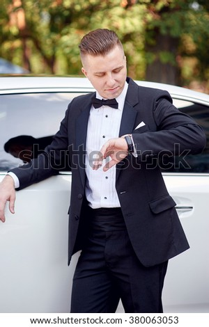 elegant stylish groom near car waiting his brite and looks at watch