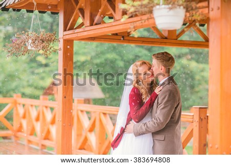 elegant stylish groom with his happy gorgeous blonde bride on the background of trees in the autumn park with red bouquet