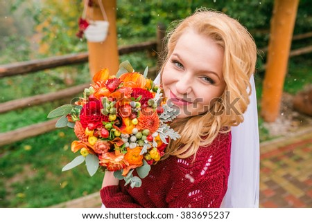 elegant stylish happy gorgeous blonde bride on the background of trees in the autumn park with red bouquet