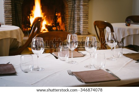 Elegant table of a restaurant near a fireplace  - stock photo