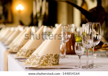 Elegant table set for a catered function with a low angle shallow depth of field view of the linen and glassware - stock photo