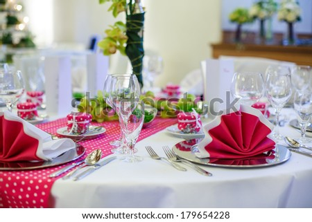 Elegant table set  for wedding or event party in pink with dots: glasses, napkins, flowers