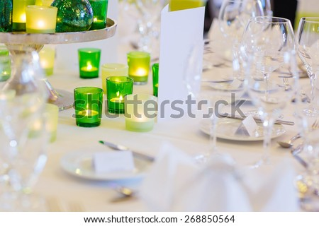 Elegant table set in green and white for wedding or event party. Flower arrangements, candles, china and porcelain tableware and napkins. Wedding details. - stock photo