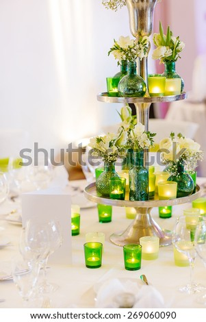 Elegant table set in green and white for wedding or event party. Flower arrangements, candles, china and porcelain tableware and napkis. Wedding details. - stock photo