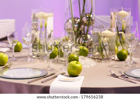 Elegant table set in green, creme and brown with apples and limes for wedding or event party - stock photo