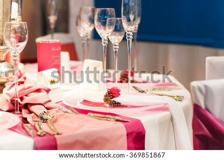 Elegant table set in soft red and pink for wedding or event party