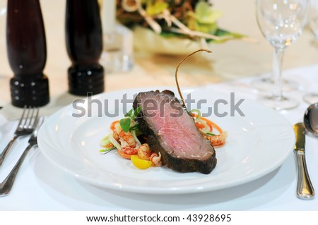 Elegant table setting for a diner in luxurious restaurant with meat on white plate.