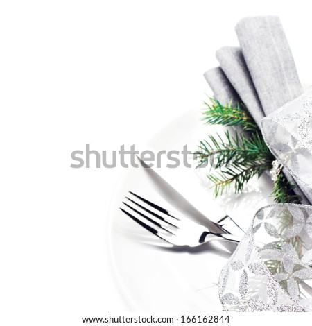 Elegant table setting place with festive decorations on white plate with silver ribbon isolated on white background, close up. - stock photo