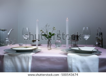 elegant table setting. romantic dinner, wine glasses, flowers in a vase, candle