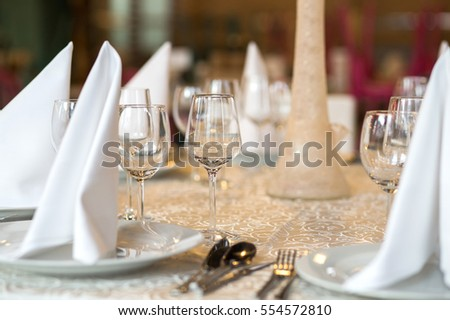 Elegant table with plates,cutlery and wine glasses