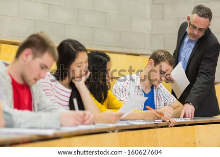 Elegant teacher with students writing notes at the college lecture hall - stock photo