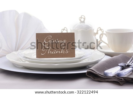 Elegant Thanksgiving table place setting with fine china, crystal and antique cutlery in subdued colors with Giving Thanks place card holder.  - stock photo
