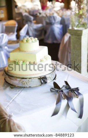 elegant tiered wedding cake (circles and square)  with knives and ribbon - stock photo