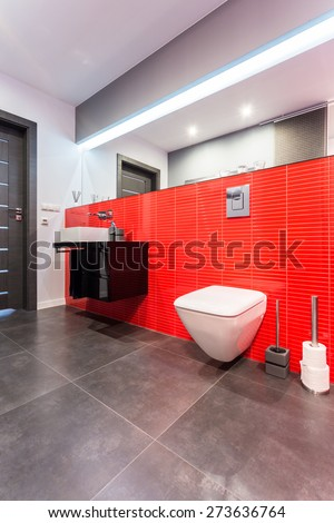 Elegant toilet with big mirror covered in red tiles - stock photo