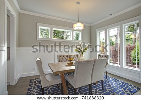 Elegant Transitional Dining Room With Board And Batten Walls Wood Table Surrounded By Grey Upholstered