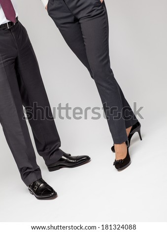 Elegant unrecognizable businessman and business lady - closeup of legs