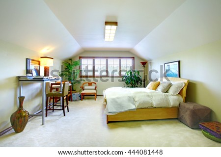 Elegant upstairs bedroom in soft tones with vaulted ceiling and study area. Decorated with plant pots. - stock photo