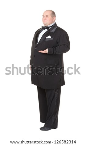 Elegant very fat man in a dinner jacket and bow tie winking mischievously and pointing with his finger across his belly , three quarter studio portrait on white - stock photo