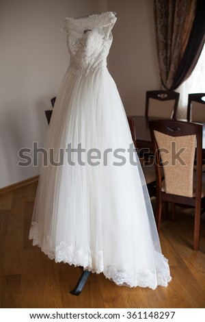 Elegant vintage white dress on a hanger in luxury hotel room
