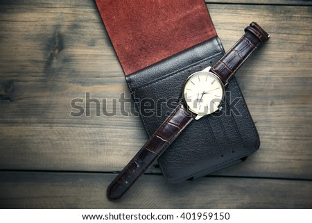 elegant watch and wallet on wooden table - stock photo