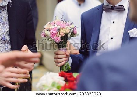elegant wedding bouquet in groom's hand - stock photo