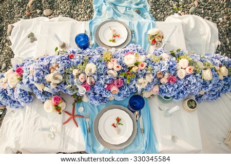 Elegant wedding reception area for bride and groom, ready for the bridal party. Rich bunch of flowers table. Sea concept. - stock photo