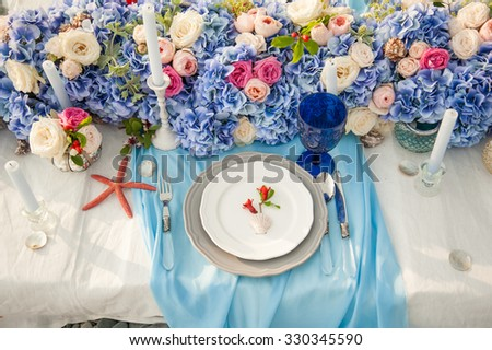 Elegant wedding reception area for bride and groom, ready for the bridal party. Rich bunch of flowers table. Sea concept.