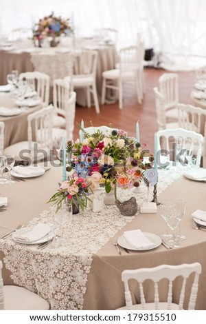 Elegant wedding reception area, ready for guests and the bridal party. Rich bunch of flowers table.